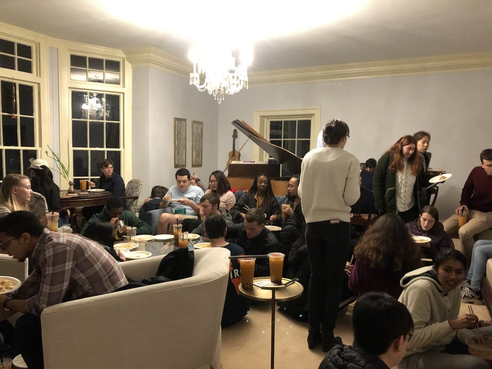 <p>IRC residents gather in the living room of Big Morea for an evening of food and celebration.</p>