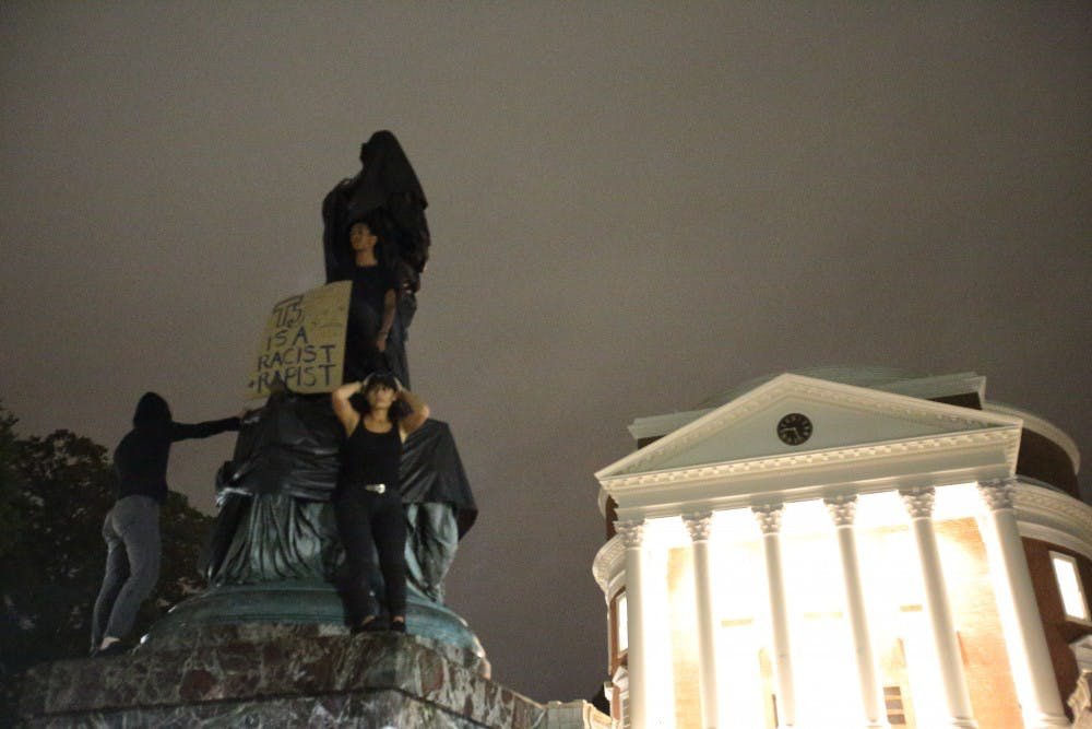 <p>Protesters stand atop the statue of Thomas Jefferson statue north of the Rotunda after shrouding it.&nbsp;</p>