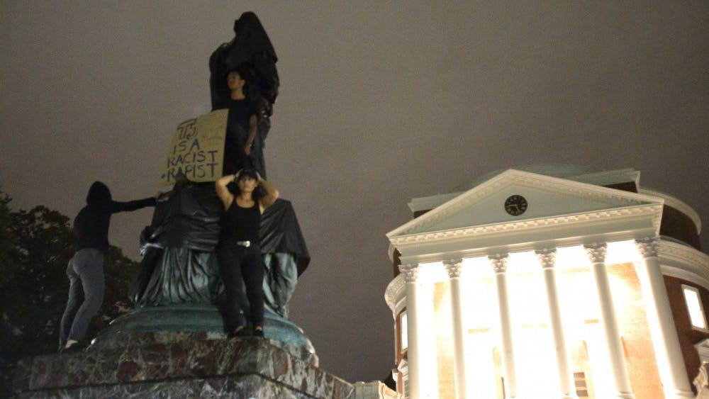 Protesters stand atop the statue of Thomas Jefferson statue north of the Rotunda after shrouding it.