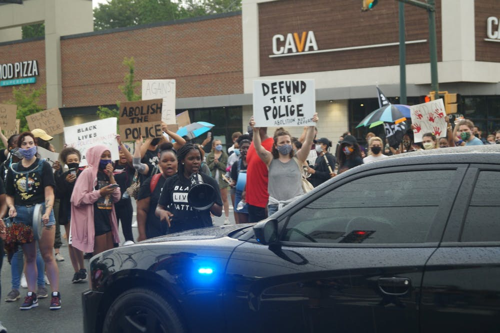 Students and community called to defund the police at a block party organized by rising second-year College student Zyahna Bryant and Trinity Hughes outside of John Paul Jones Arena June 13.