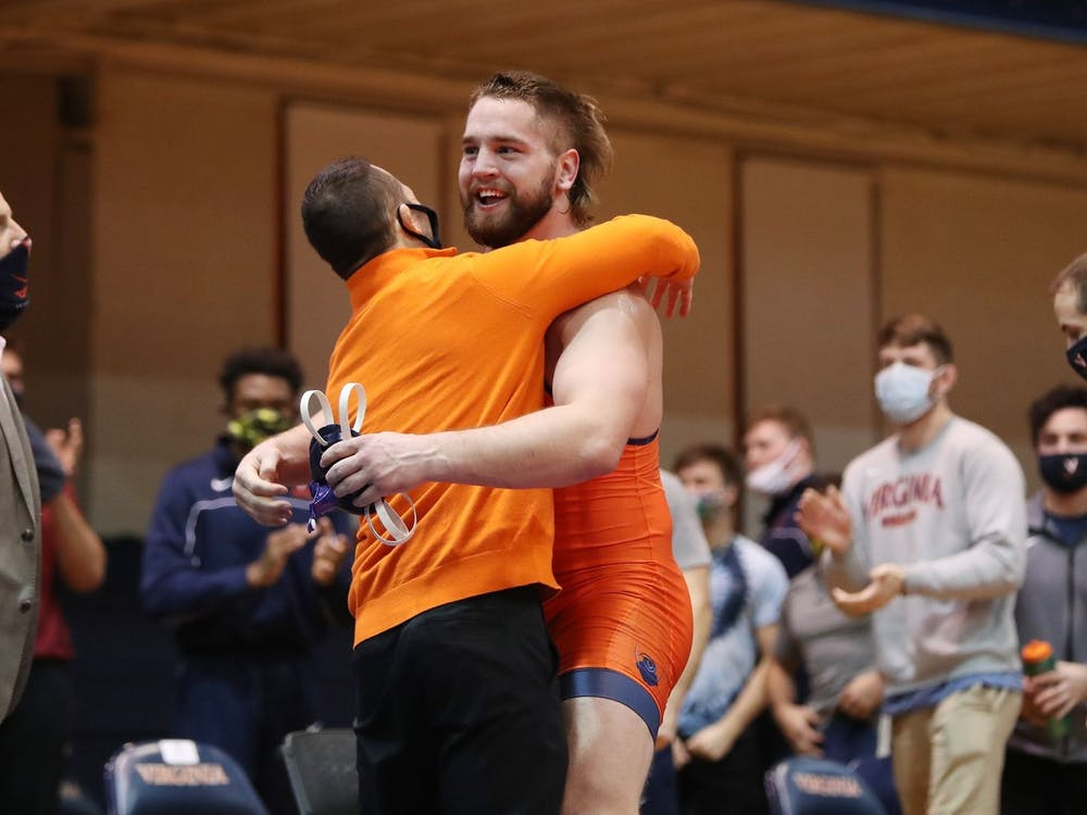 Sophomore Quinn Miller celebrates with Coach Steve Garland after earning a major decision victory to give Virginia the win.