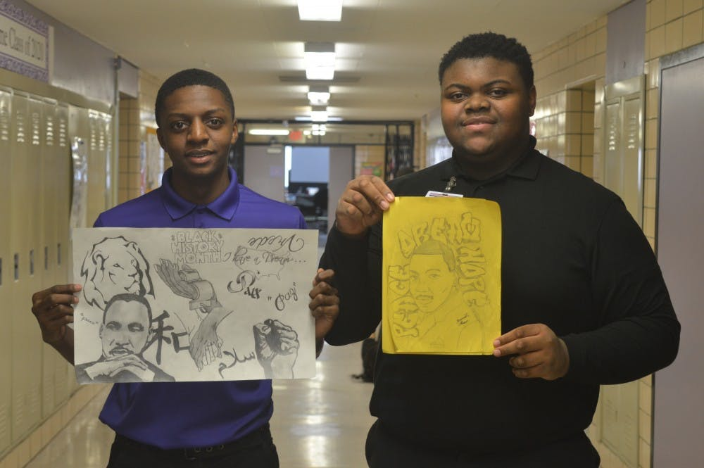 <p>Sophomore Caleb Bailey, left,&nbsp; and junior&nbsp;Jeremiah Flowers hold pieces of outstanding artwork of the late Martin Luther King Jr.</p>