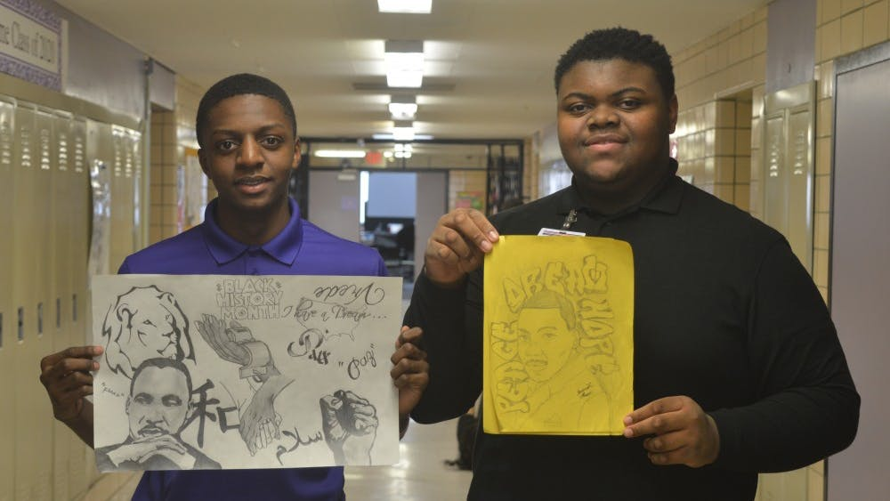 Sophomore Caleb Bailey, left, and juniorJeremiah Flowers hold pieces of outstanding artwork of the late Martin Luther King Jr.
