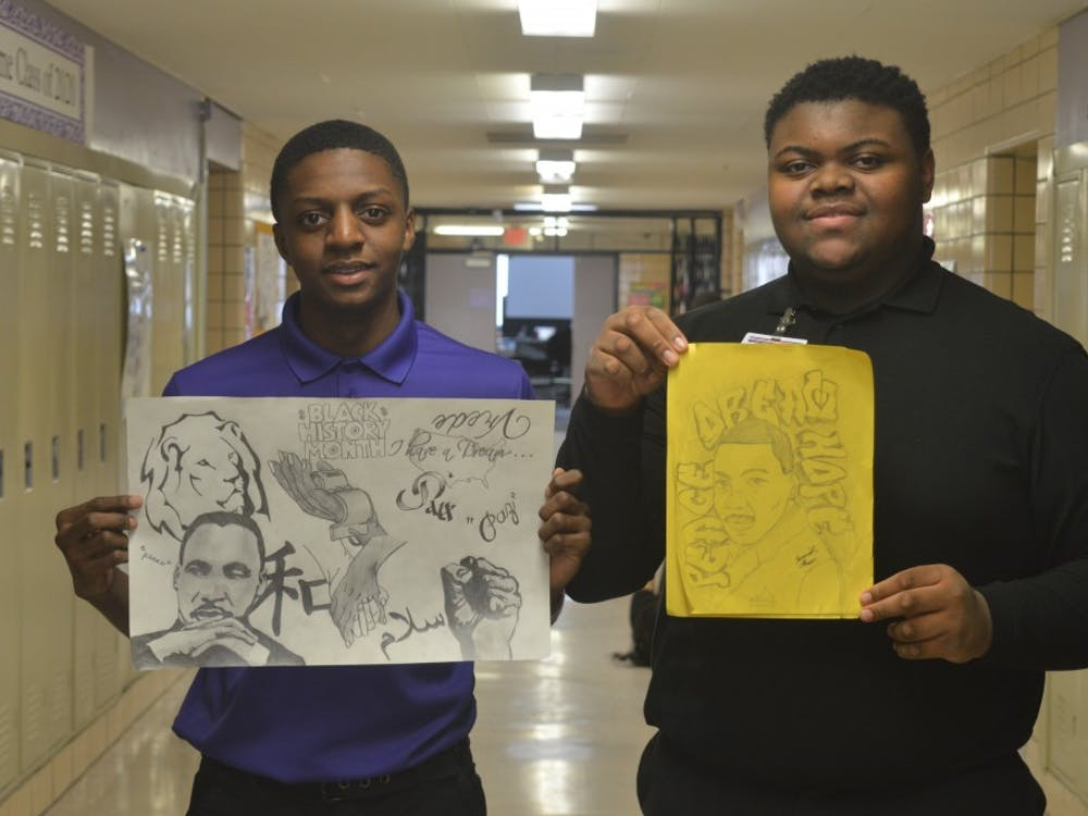 Sophomore Caleb Bailey, left,  and junior Jeremiah Flowers hold pieces of outstanding artwork of the late Martin Luther King Jr.
