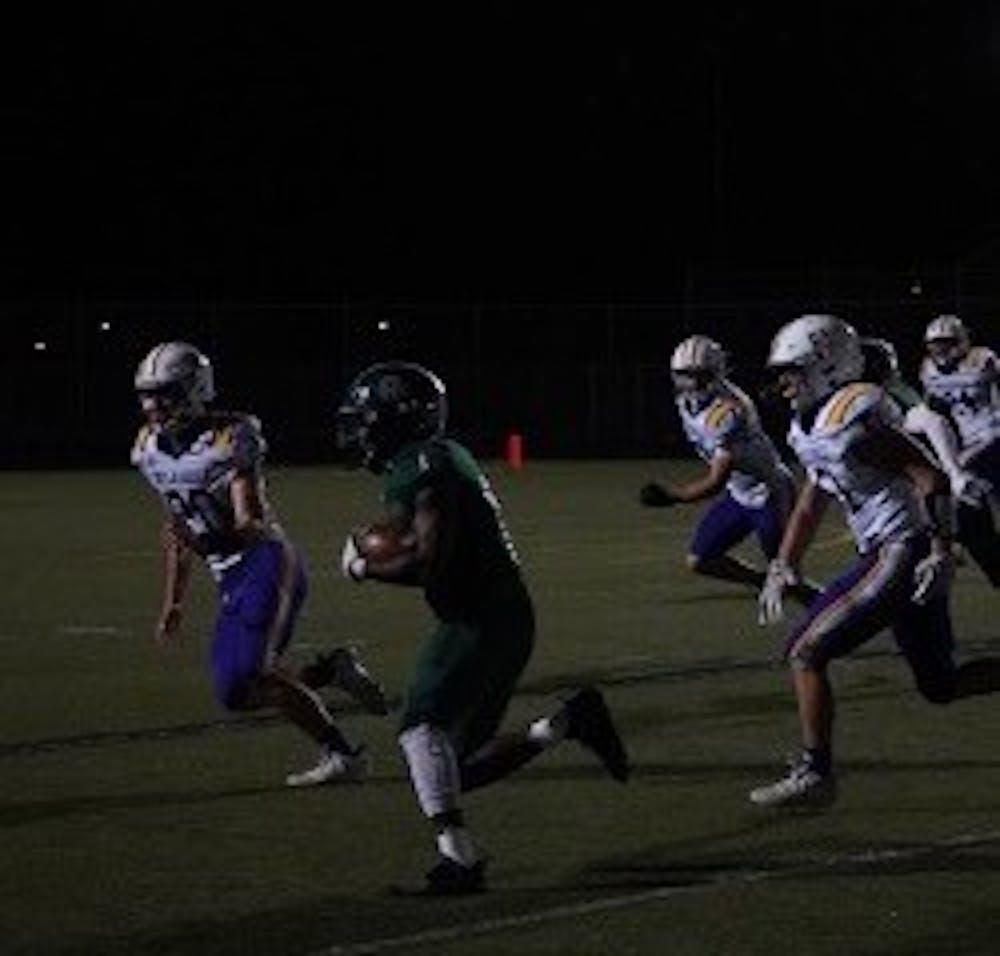 <p>Senior running back Brent Parker moves past the defense. Photo by Quinten Love.</p>