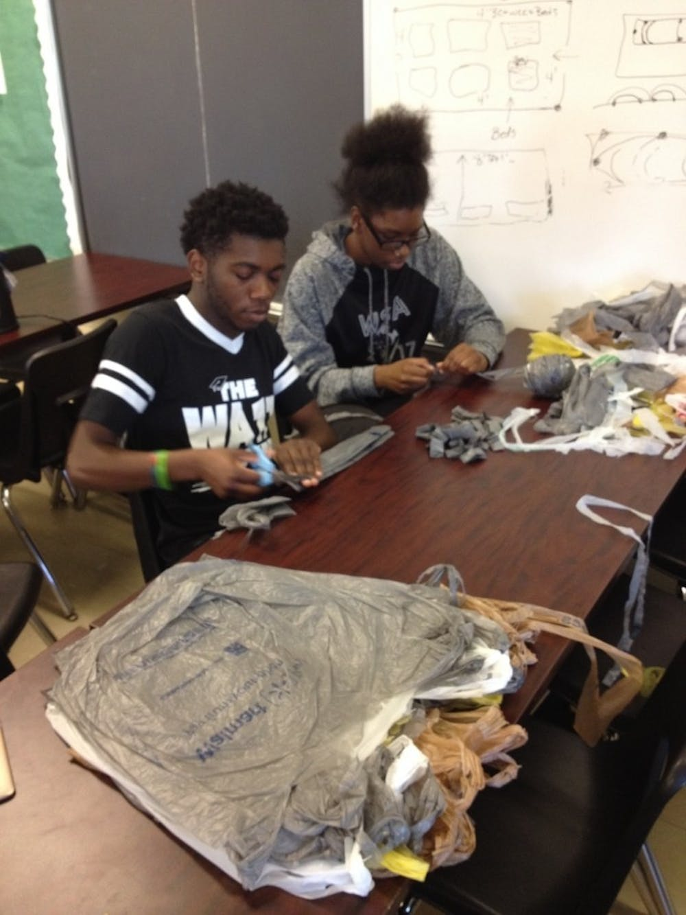 <p>Seniors Shaylan Harden and&nbsp;Taja Evans work meticulously to create their blanket.&nbsp;</p>