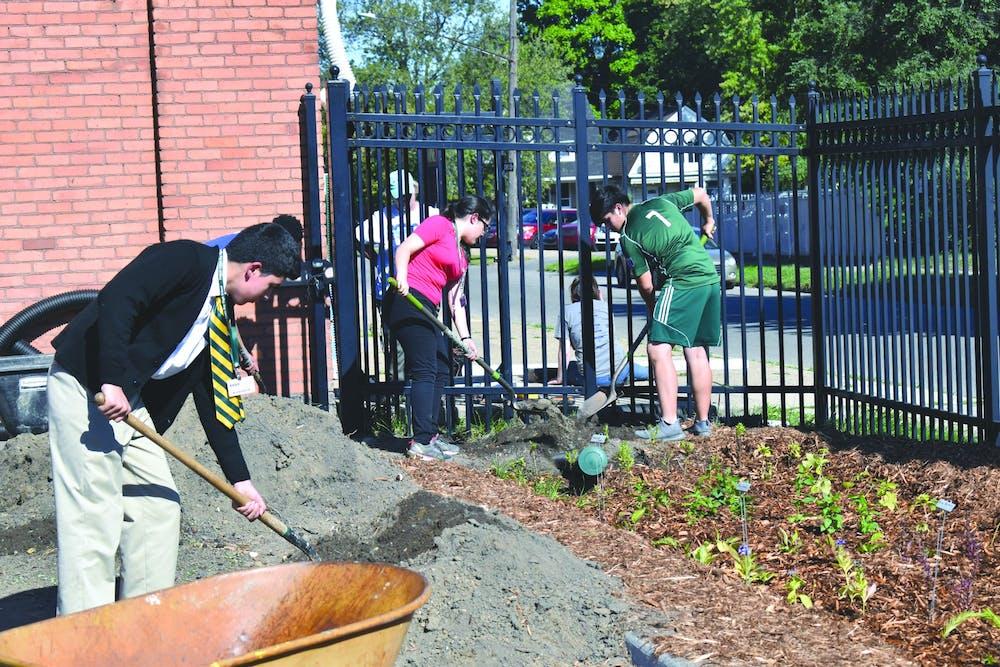 <p>Cristo Rey students move soil to create the rain garden. Photo by Ivar Arias-Hernandez.</p>