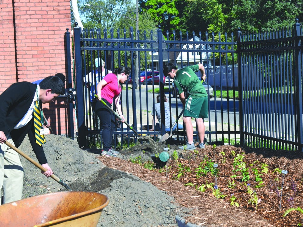 Cristo Rey students move soil to create the rain garden. Photo by Ivar Arias-Hernandez.
