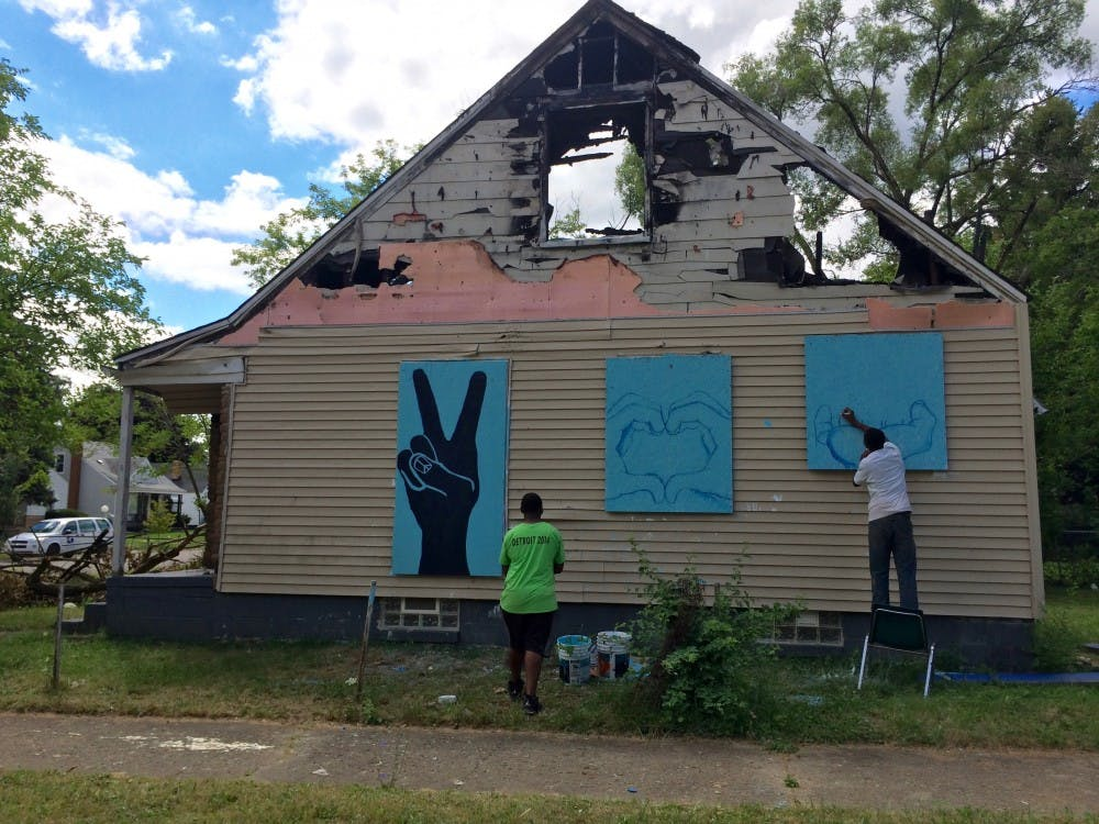 Former DIT student Samuel Bessiake paints murals on an abandoned house across from the entrance to Cody DIT about a month before the house was torn down. A neighbor stopped the crew and asked them to save the murals, which were moved to another vacant house.