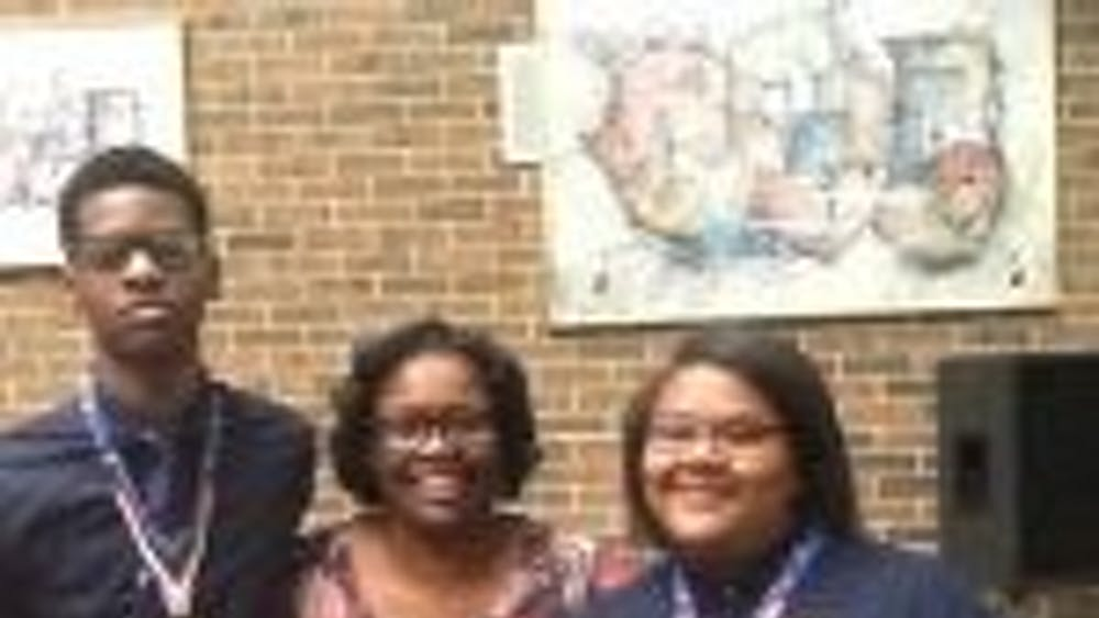 Nicolas Huey, far left and Kharriane Gray far right picturedwith their 11th grade English Teacher, Ms. Allayne Woods. Ms. Woods inspired Gray and Huey to submit their essays for the study abroad program.