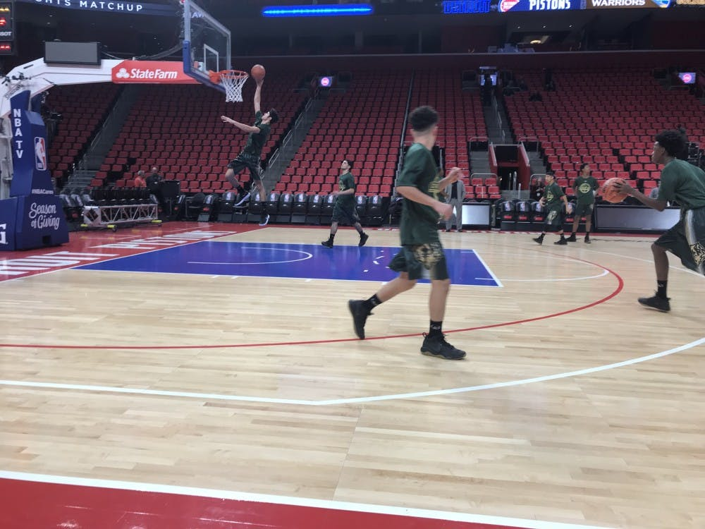 The Varsity Wolves warm up before the game at Little Caesars Arena.