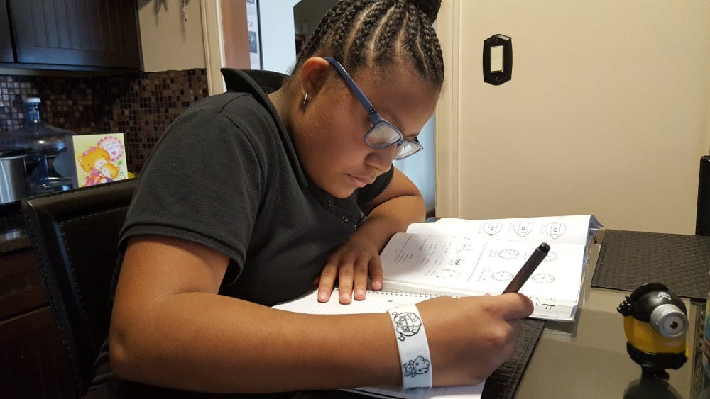 <p>Foreign Language Immersion student Anaya Smith completes her Japanese homework at the kitchen table.</p>