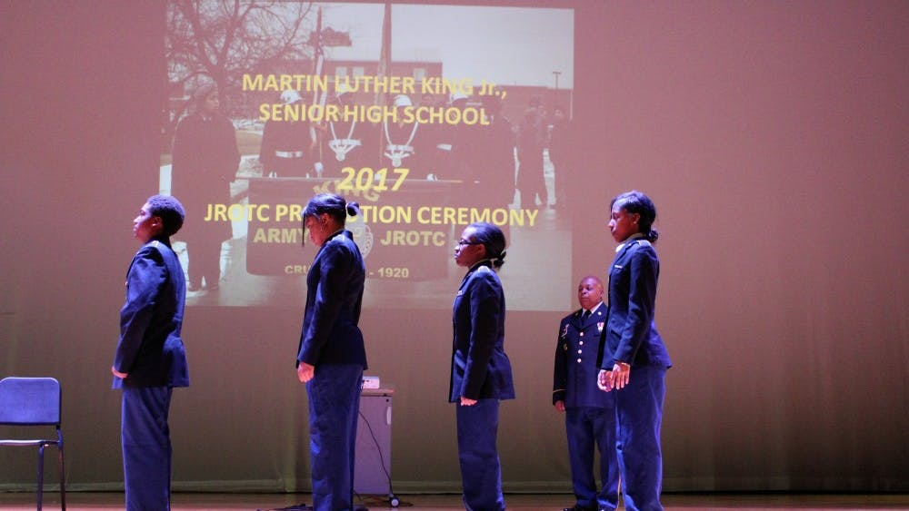 Cadets Larry Collier (freshman), Taylor Jackson (senior), Kelsey Gee (sophomore), and Darshay Burrell (sophomore) prepare to be pinned by their parents. Sergeant first class Jamille Phillips (in the back) gives the orders.