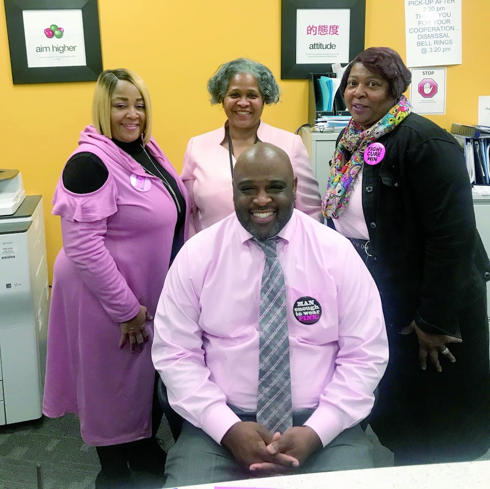 <p>East English Village principle Dr. Larry Gray, seated, and his administrative staff participated in Pink Out Day on Oct. 14.</p>