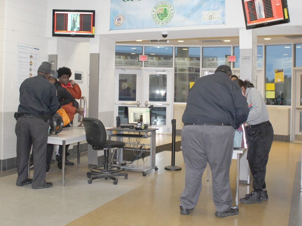 Security staff checks students and adults as they enter the building through metal detectors. This and other procedures are in place to ensure safety.