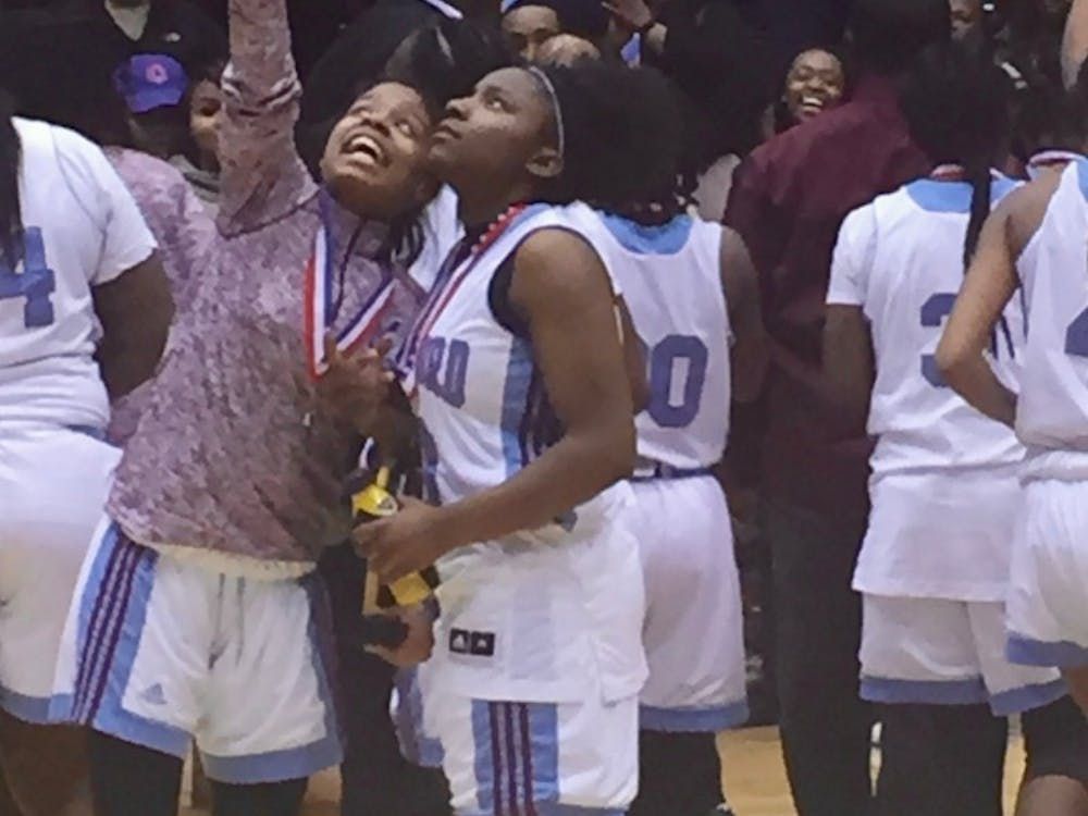 Mumford varsity basketball teammates TaSharRay Anderson and Adoreya Williams check out the scoreboard after winning the PSL championship at Calihan Hall on Feb. 16.