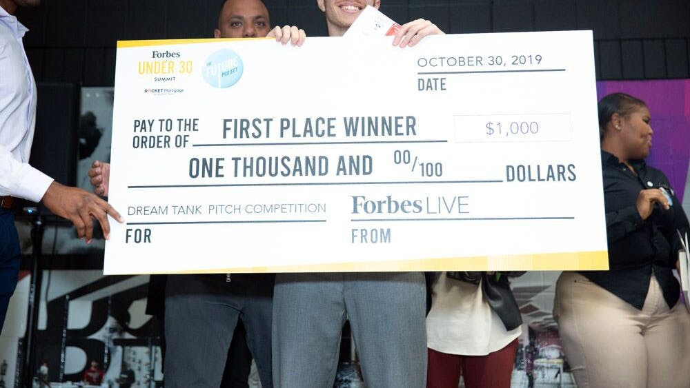 "Davon Schelgel holds the first place check from the ""Shark Tank""-style competition. Competitors had to pitch their business ideas to win a $1,000 starting check provided by Forbes. Courtesy photo."