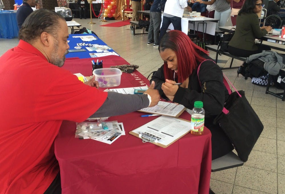 <p>Darwin Griffin from Metro Detroit&nbsp;AFL-CIO&nbsp;helps junior Tiyatta Young fill out a voter registration form during Mumford's 2nd Annual Career Day Expo on Feb. 16.&nbsp;</p>
