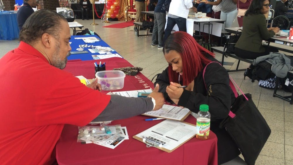 Darwin Griffin from Metro Detroit AFL-CIO helps junior Tiyatta Young fill out a voter registration form during Mumford's 2nd Annual Career Day Expo on Feb. 16.
