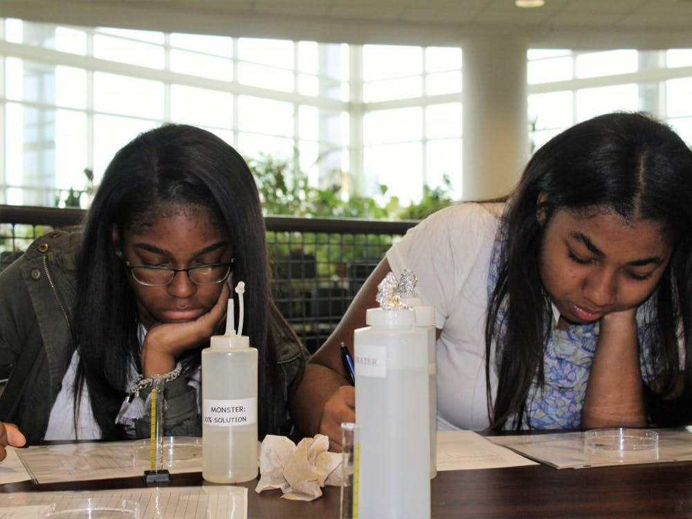 Seniors Ariana Foster and Camryne Stubblefield complete a DAPCEP experiment on the consequences of energy drinks.