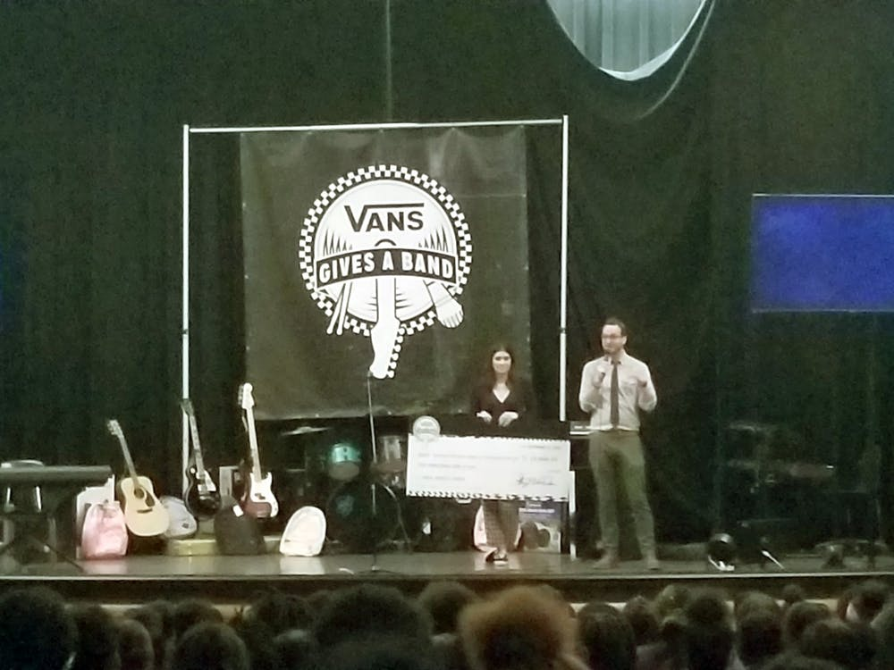 Benjamin Piper accepts check and instruments from the Vans after receiving a grant.