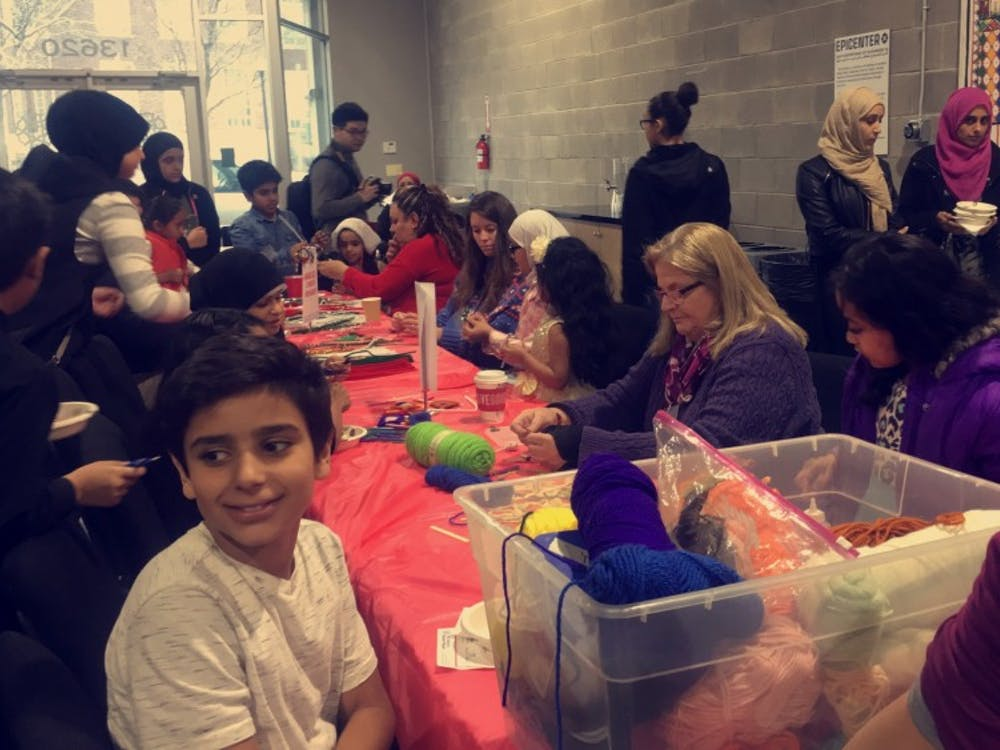 Cristo Rey staff and students help children make crafts at the National Arab American Museum's Christmas party.