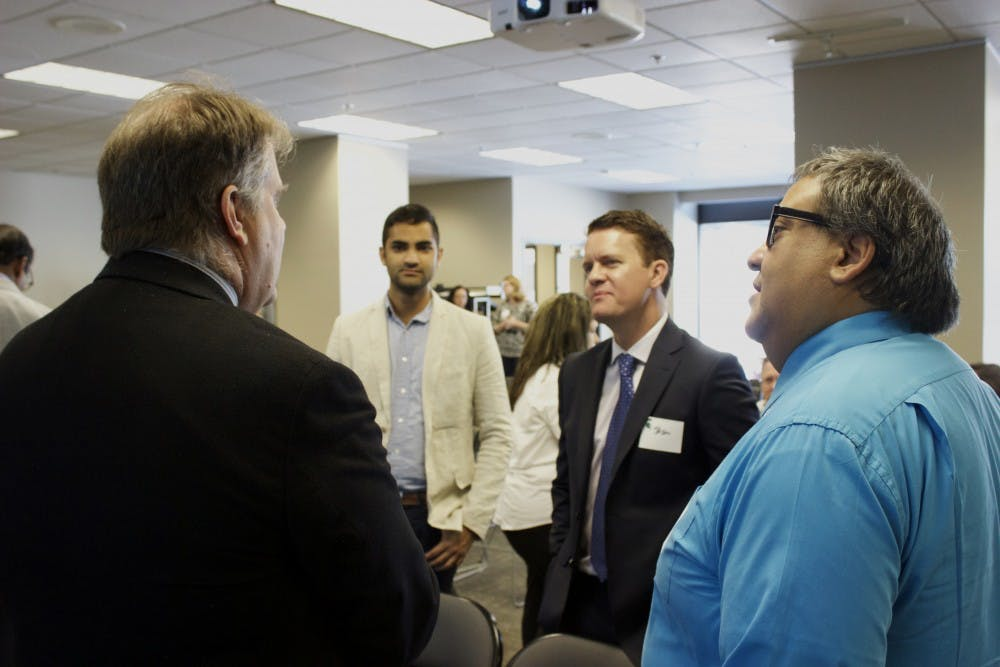 Michigan State University School of Journalism Editor in Residence Joe Grimm, left, talks with Jason Stein, publisher of Automotive News and other Crain staff members.