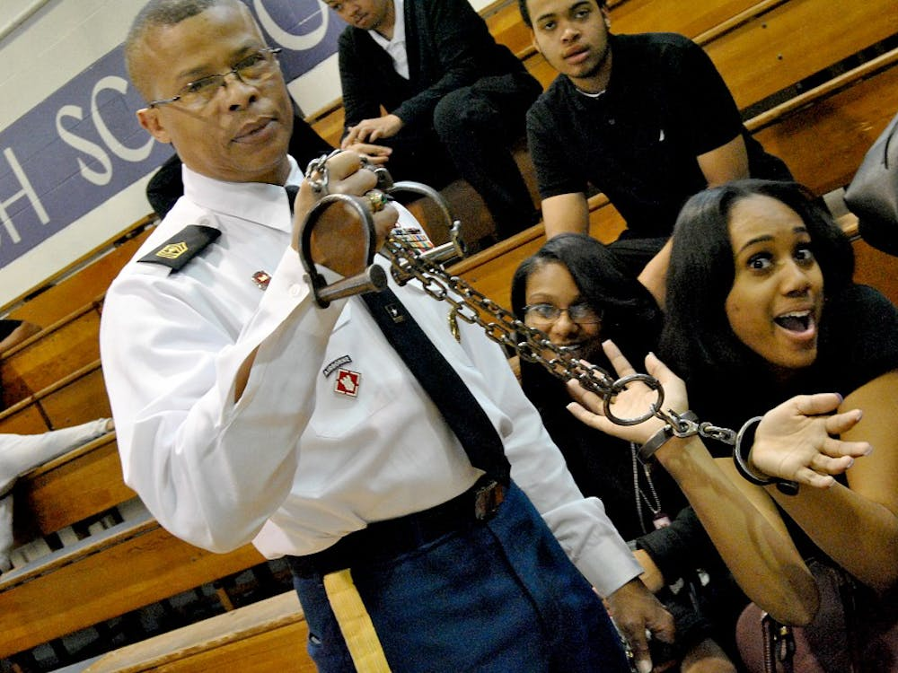 1st Sgt. Gentry hand cuffs Senior De'Aira Everette during the Black History Program.
