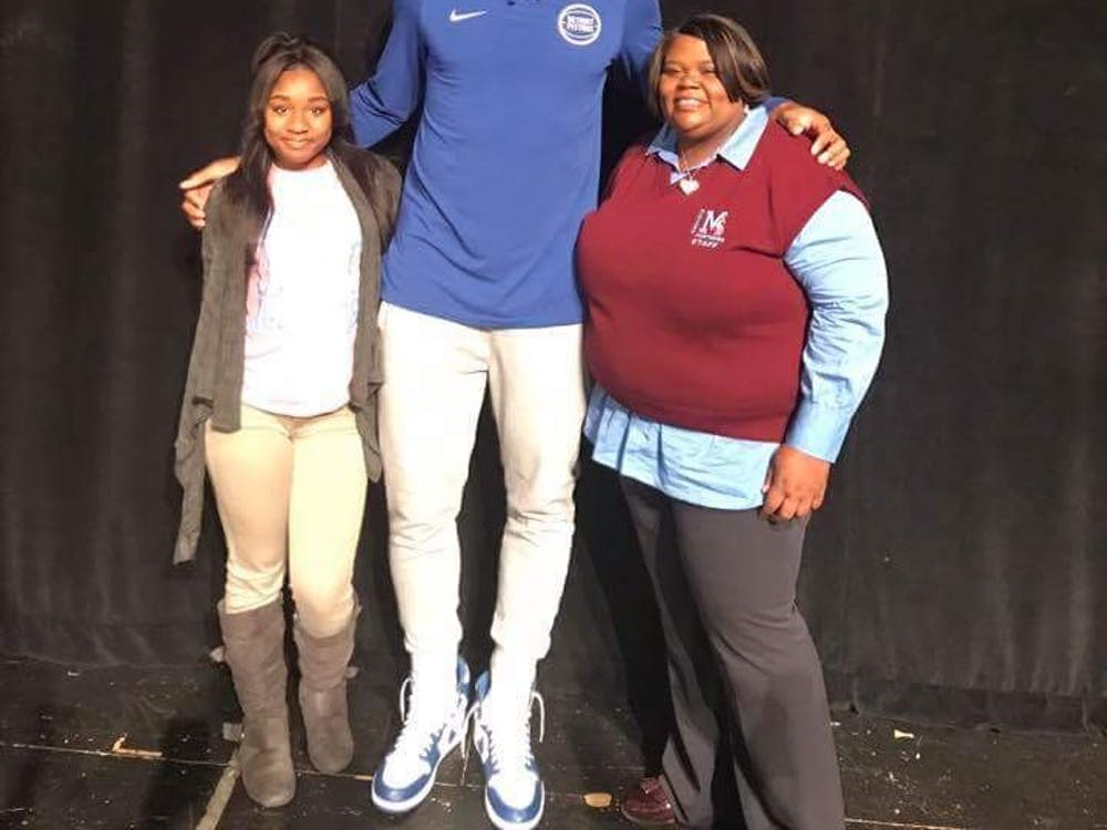 (Staff Photo/Mustang Voice) Detroit Piston Andre Drummond poses with senior Ebony Norwood and Mumford H.S. Principal Angela Prince on Oct. 24 after awarding the school with prizes for a winning video produced by Norwood.
