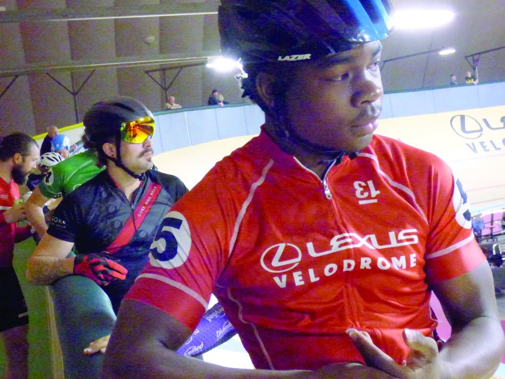 <p>Jackson Capela listens to the official before the start of a race at the Velodrome in downtown Detroit on Oct. 26. He's been riding competitively for two years. Photo by Logen Merritt.</p>