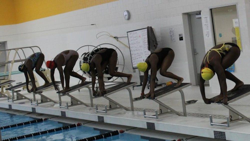 Girls' swim team prepare before the city championship swim meet.