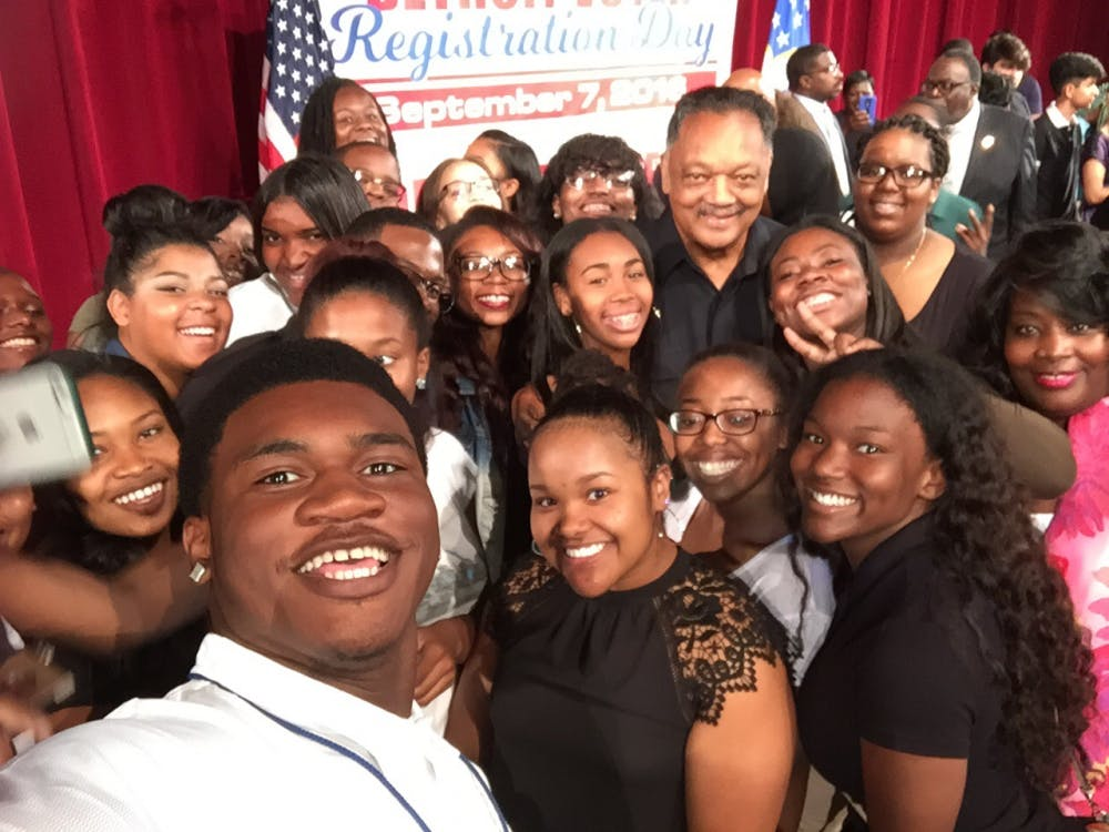 Principal Lisa Phillips and civil rights activist Jesse Jackson take aselfie with Cass Tech seniorsfollowing his inspiring speech during Cass Tech's National Registration Day Rally onSept. 7.