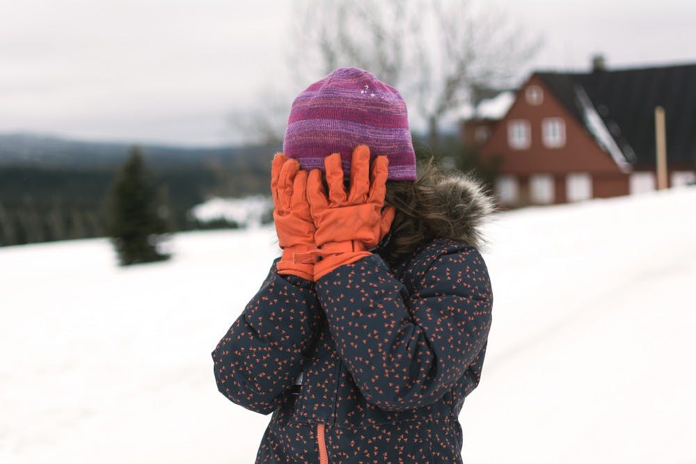 little-girl-covers-her-face-in-winter