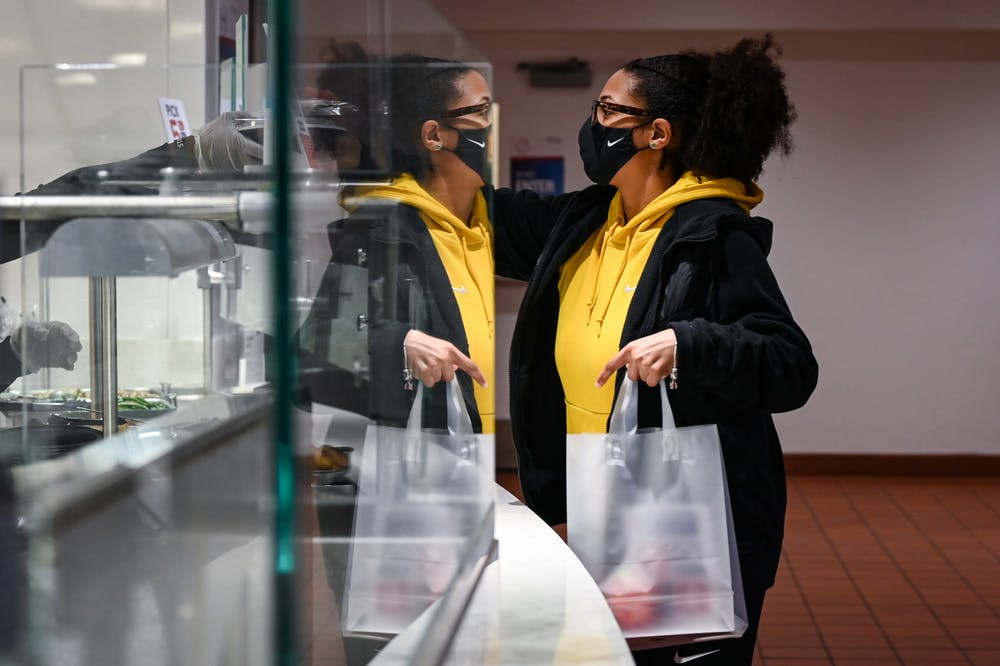 01-14-21-hill-dining-hall-student-in-mask-getting-food-kylie-cooper-jpg