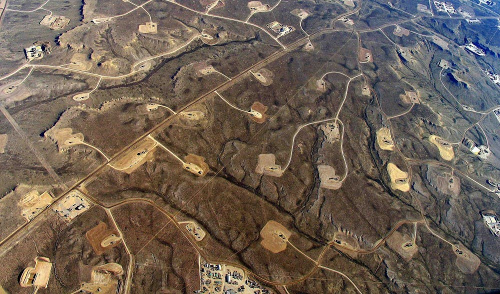 Areas with heavy fracking activity are marked by patterns of pipelines, roads, and well pads.
