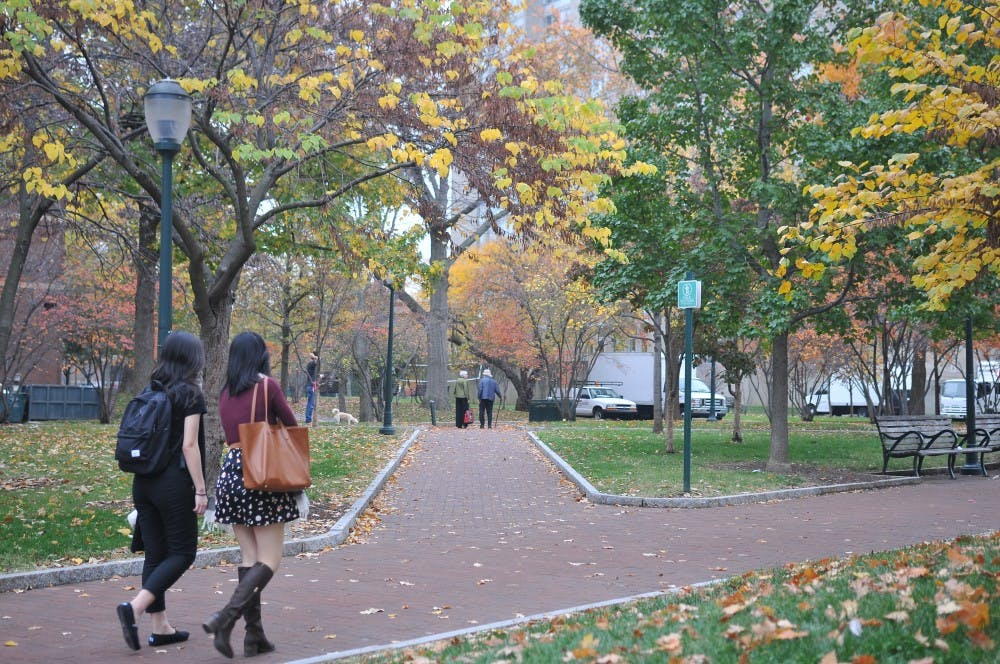 Students walked past by the High Rise Fields, where trees showed signs of autumn.