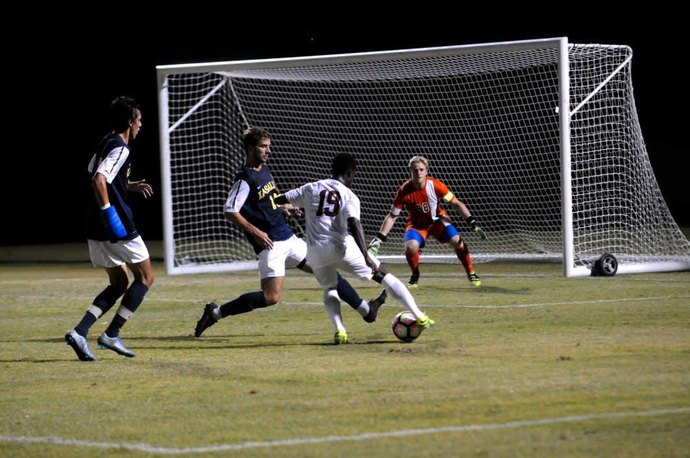 Freshman Midfielder Dami Omitaomu dribbles around La Salle defenders.