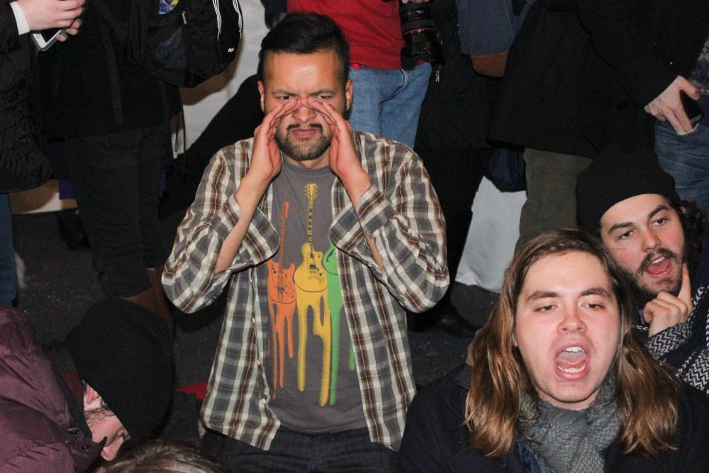 College seniorEmanuel Martinez, one of the protest's leaders, sits at President Amy Gutmann's holiday party after Gutmann addressed the crowd.