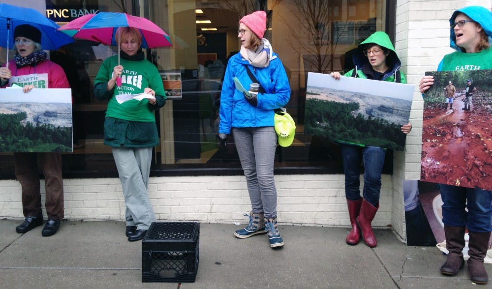Activists protest PNC's financing of coal mining expeditions.