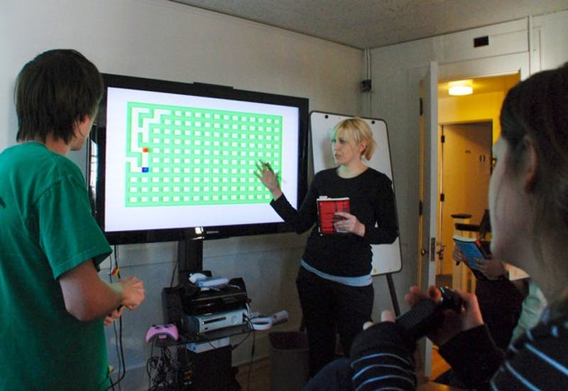 Professor Mary Flanagan and her students examine a vintage video game in the newly-opened Tiltfactor Lab, a game design center in North Fairbanks Hall that houses many antique and modern gaming consoles.