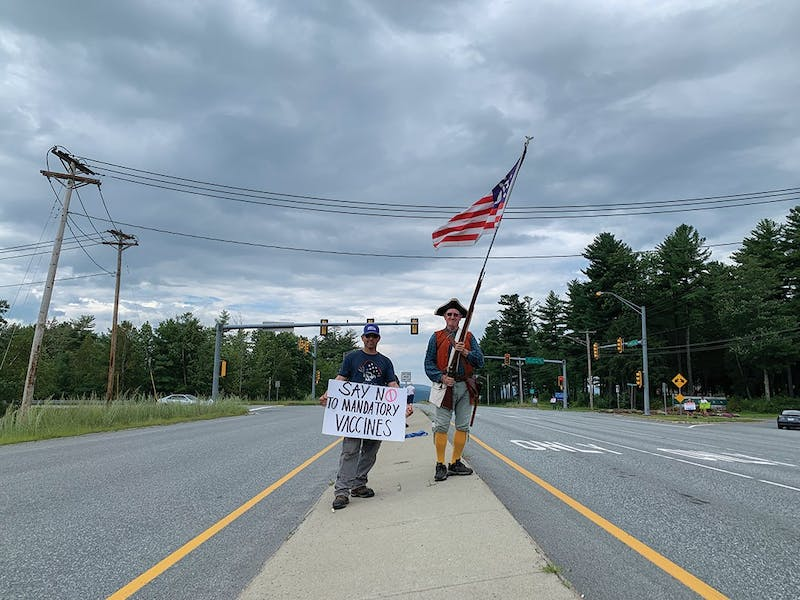 Wayne Mitchell, right, and another protester, left, stood in the median on Route 120, cheerfully waving a sign and flag at passing cars.