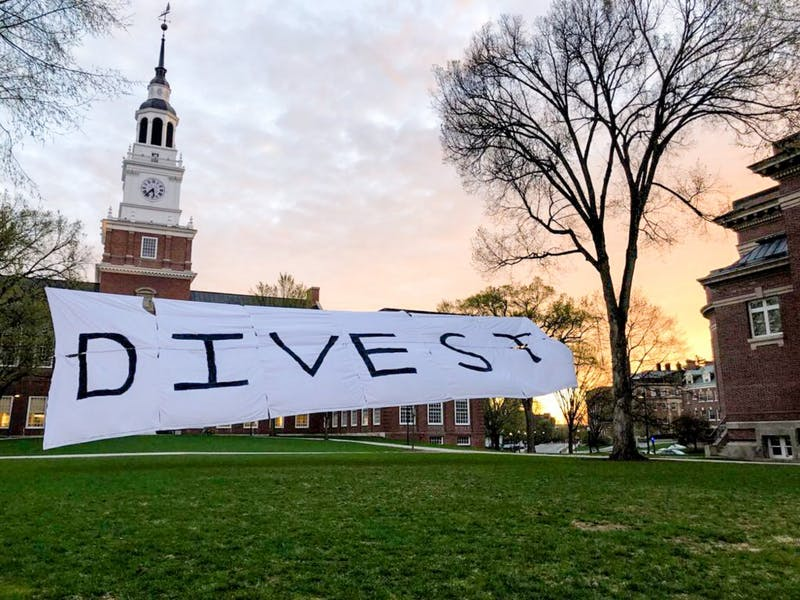 The banner that Divest Darmouth unfurled in front of Baker-Berry Library serves as an example of the sorts of activism the organization has recently undertaken.