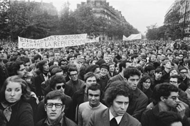 In this photograph, Strambourg captures a crowd of marching protestors holding a sign that reads