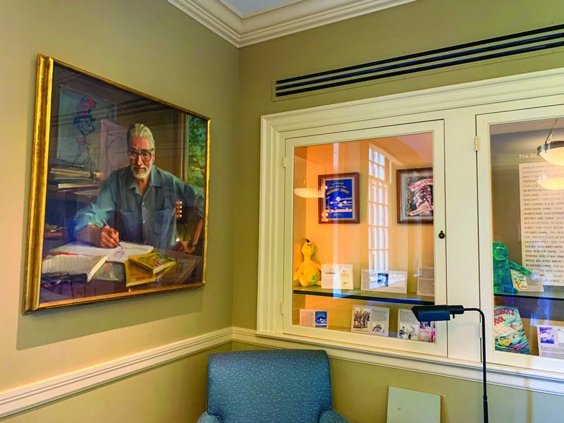 A portrait of Theodor Geisel '25 hangs in the Dr. Seuss Room, along with books and other paraphernalia.