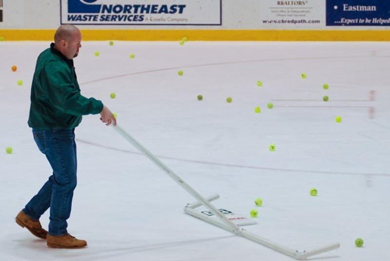 A Thompson Arena staff member cleans up tennis balls thrown onto the ice after the Big Green scored its first goal during last year's Princeton game.