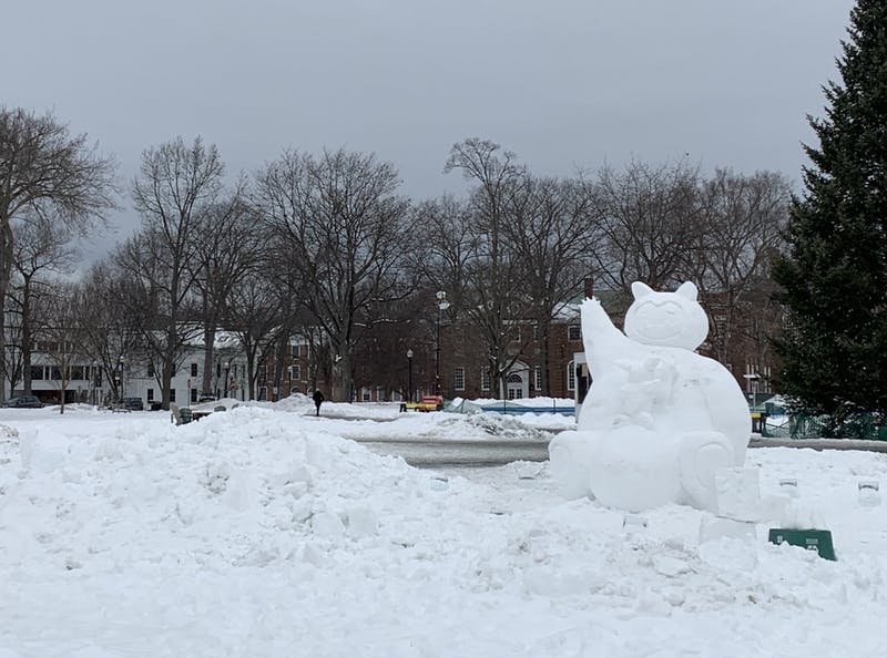 One of three Winter Carnival snow sculptures, a Pokémon Snorlax waves at campus from the Green.