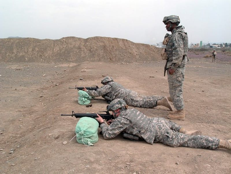 1st Lt. Liz Hunt '05, the soldier lying in the front of the foreground above, practices at a range with two fellow soldiers serving in Afghanistan.