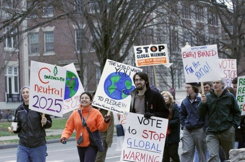 Students and town residents march on East Wheelock Street to raise awareness about global warming.