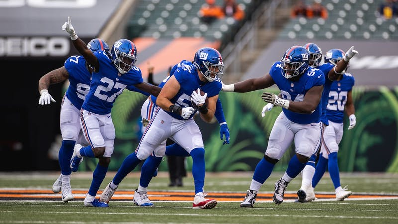 Niko Lalos '20 (57) is cheered on by his New York Giants teammates after recording an interception in his NFL debut.