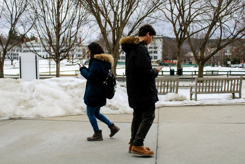 Students glance at their phones as they walk through the campus.